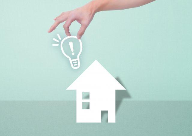 電球を掴む手と家の模型
